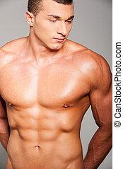ficar, força, jovem, muscular, cinzento, enquanto, posar, contra, fundo, masculinity., bonito, homem
