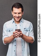 ficar, grande, seu, jovem, contra, cinzento, alegre, enquanto, smartphone, fundo, usando, sorrizo, message!, homem