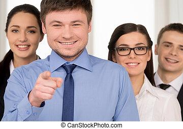 ficar, grupo, negócio, apontar, pessoas, sucedido, câmera., dedo, fundo, homem sorridente