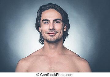 ficar, handsome., shirtless, cinzento, contra, olhando jovem, confiante, enquanto, câmera, fundo, retrato, homem sorridente