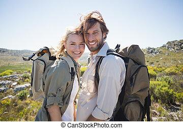 ficar, montanha, par hiking, terreno, câmera, sorrindo