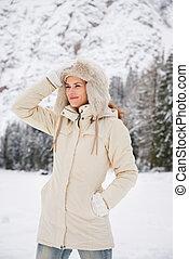 ficar, mulher, casaco inverno, ajustar, enquanto, ao ar livre, chapéu
