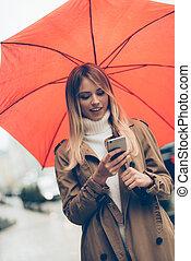 ficar, mulher, guarda-chuva, dela, connected., móvel, always, olhando jovem, telefone, enquanto, carregar, rua, atraente, sorrindo