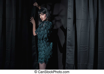 ficar, mulher, room., escuro, moda, feiticeira, segurando, curtain.