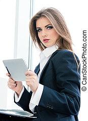ficar, mulher, tabuleta, dela, relaxado, jovem, negócio, pc, enquanto, janela, usando, escritório