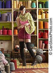 ficar, mulher, tricotando, jovem, fio, frente, exposição, echarpe