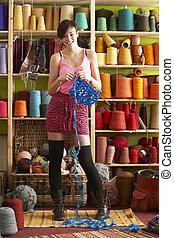 ficar, mulher, tricotando, jovem, fio, segurando, frente, exposição