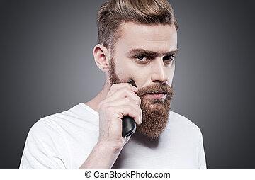 ficar, navalha, barbudo, seu, elétrico, câmera, cinzento, contra, olhando jovem, confiante, enquanto, perfect., barba, fundo, fazer, homem, raspar