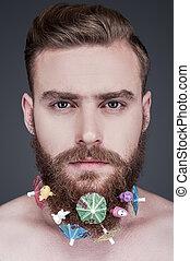 ficar, partido, seu, coquetel, beard., cinzento, shirtless, jovem, contra, parasols, olhar, enquanto, câmera, fundo, brinquedos, homem, retrato, barba, bonito