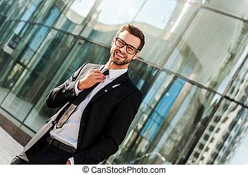 ficar, predios, seu, escritório, gravata, sucedido, ajustar, olhando jovem, enquanto, câmera, businessman., fundo, ao ar livre, homem negócios, sorrindo