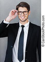 ficar, seu, ajustar, jovem, formalwear, cinzento, confiante, enquanto, óculos, businessman., contra, fundo, homem sorridente, bonito