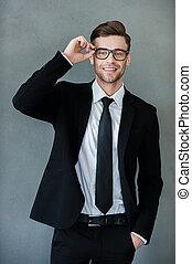 ficar, seu, business., ajustar, cinzento, contra, olhando jovem, enquanto, câmera, fundo, pronto, homem negócios, eyewear, feliz