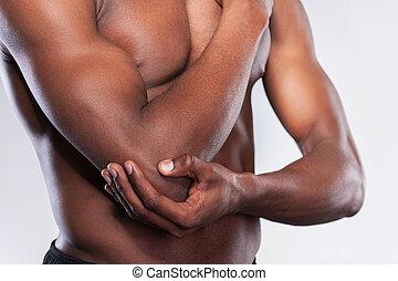 ficar, seu, dor, muscular, imagem, jovem, recortado, cinzento, enquanto, tocar, contra, fundo, africano, cotovelo, elbow., homem