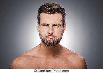 ficar, shirtless, cinzento, contra, olhando jovem, enquanto, câmera, grimacing., fundo, grimacing, retrato, homem