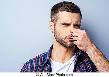 ficar, smell., camisa, jovem, contra, cinzento, enquanto, repugnar, nariz, fundo, segurando, retrato, homem, frustrado, casual, negativity, expressar