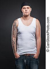 ficar, tatuagem, looking., segurando, jovem, mão, bolsos, mãos, sujeito, homem, fresco