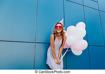 ficar, urbano, mulher, parede, chapéu, aniversário, balões, feliz