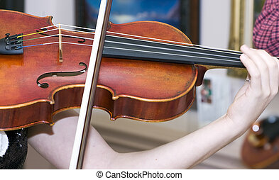 A close up of a violin or fiddle player strumming her violin or fiddle.