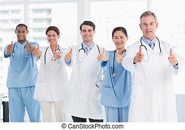 fiducioso, dottori, gesturing, pollici, a, ospedale