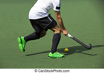 Field Hockey - Field hockey player, in possesion of the...
