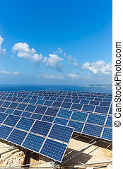 Field of solar collectors near sea with blue sky