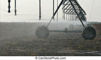 Field watering equipment splashing water - Sprinkler at...