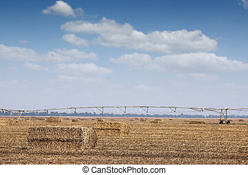 field with straw bale and center pivot sprinkler system