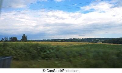 fields through the fast running train window