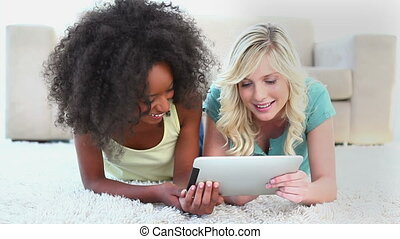 Fiends laughing while using an ebook against white...