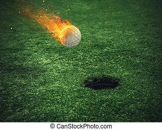 Fiery golf ball near the hole in a grass field - Fiery golf...
