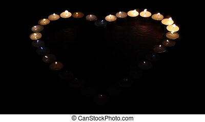 Fiery heart - Candles are lit in the shape of hearts and...