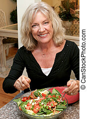 A beautiful woman in her fifties staying fit by eating healthy.