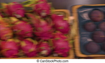 Fig and dragon fruit in a basket - A pan to left shot of...