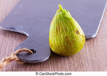 Fig - Green fig standing near a black chopping board