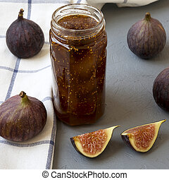 Fig jam in glass jar and fresh figs on concrete background, side view. Close-up.