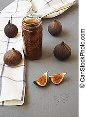 Fig jam in glass jar and fresh figs on grey background, side view. Close-up.