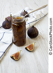 Fig jam in glass jar and fresh figs on white wooden background, side view. Close-up.