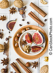 Fig walnuts cinnamon anise on a plate of old wooden background.