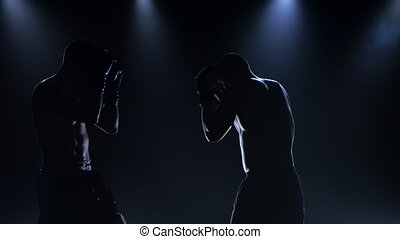 Fight of two boxers in studio on a dark background