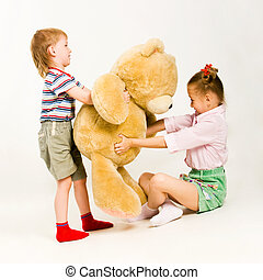 Fight - Photo of little boy and girl trying to take teddy...