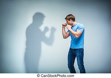 Fight - Young man with shadow in studio
