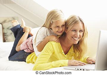 figlia, rilassante, seduta, divano, laptop, usando, madre, casa