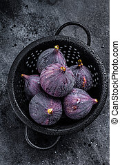 Figs in a colander, organic fruit. Black background. Top view