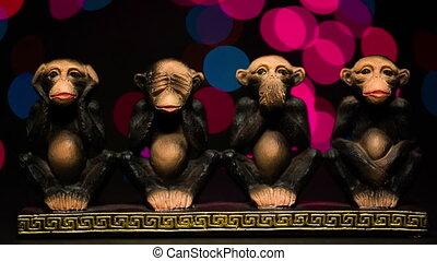 Figure four symbolic monkeys on bokeh background. Close up...