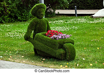 Figure of a man with a cart made of grass