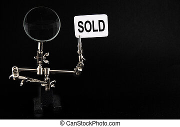 """figure of steel man with """"sold"""" inscription"""