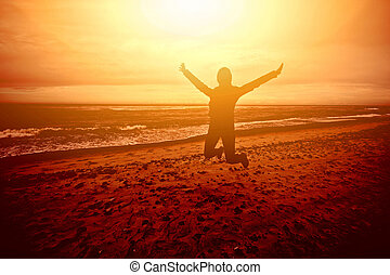 Figure person jumping on the beach at sunset.