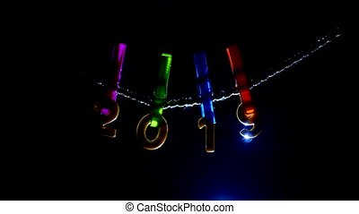 Figures 2019 hanging on clothespins and a rope on a black background that backlight will shine on, close-up, symbol, Xmas, the new year 2019