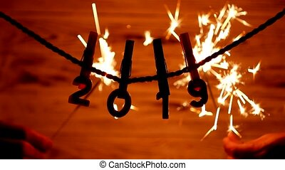 Figures 2019 hanging on clothespins and rope, sparklers burning in the background, new year 2019, Christmas, New Year holidays, sparks, burning