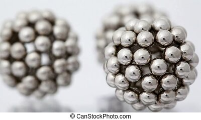 figures consisting of metallic balls rotate around its axis